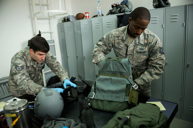 U.S. Air Force Staff Sgt. Kevin Ray, left, and Tech. Sgt. Nathanial Robinson Jr., right, both 74th Expeditionary Fighter Squadron aircrew flight equipment technicians from the 23rd Operations Support Squadron at Moody Air Force Base, Ga., check survival equipment during the 74th EFS's deployment in support of Operation Atlantic Resolve at Graf Ignatievo, Bulgaria, March 16, 2016. Aircrew flight equipment technicians inspect and repair all gear issued before and after every flight. (U.S. Air Force photo by Staff Sgt. Joe W. McFadden/Released)
