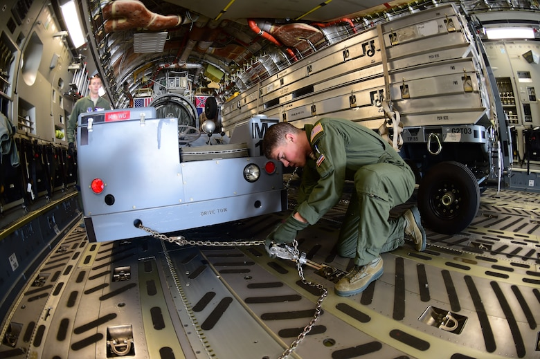 Airman 1st Class Harris Williams, 172nd Airlift Wing loadmaster, locks down cargo in a C-17 Globemaster III March 15, 2016, on Buckley Air Force Base, Colo. The aircraft from the 172nd Airlift Wing, Jackson, Mississippi, helped the 140th Wing transport equipment down to Tyndall AFB, Florida, for an exercise. (U.S. Air Force photo by Airman 1st Class Luke W. Nowakowski/Released)