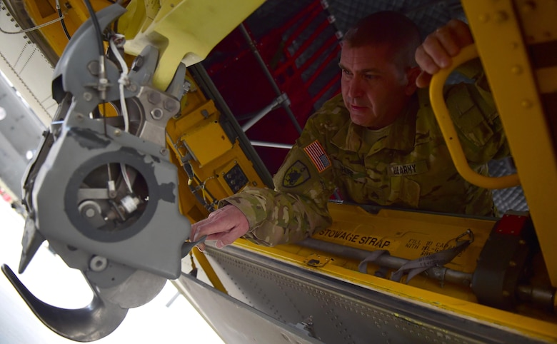 U.S. Army Staff Sgt. Wade Shore, Colorado Army National Guard CH-47 crew chief, demonstrates how the sling load hook moves in a helicopter March 3, 2016, at the Army Aviation Support Facility on Buckley Air Force Base, Colo. While in flight, the Chinook crew chief, utilizes the sling load hook to maneuver the helicopter's load. (U.S. Air Force photo by Airman 1st Class Gabrielle Spradling/Released)