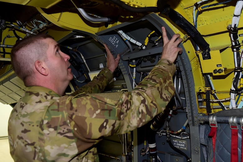U.S. Army Staff Sgt. Wade Shore, Colorado Army National Guard CH-47 crew chief, displays part of the Chinook helicopter that he is accountable for maintaining March 3, 2016, at the Army Aviation Support Facility on Buckley Air Force Base, Colo. Crew chiefs must maintain the aircraft, crew, load, and passengers' safety before, during and after flight. (U.S. Air Force photo by Airman 1st Class Gabrielle Spradling/Released)