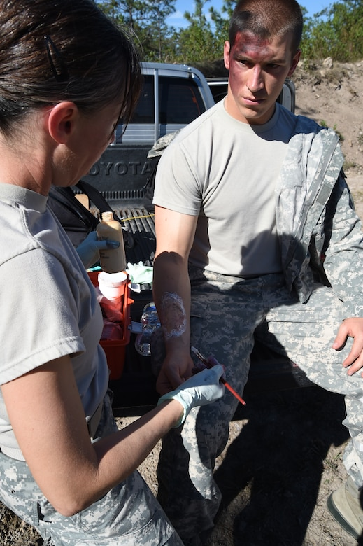Staff Sgt. Yanna Ramaekers (left), Joint Task Force-Bravo Medical Element medic, applies simulated wounds, or moulage, on 1Lt. Andrew Lankow, Joint Task Force-Bravo Ports and Plans officer in charge, March 10, 2016 near Soto Cano Air Base, Honduras, for a simulated personnel recovery exercise. 1Lt. Lankow played a UH-60 Black Hawk helicopter crash victim for this exercise which involved both Honduran forces and Servicemembers from JTF-Bravo. (U.S. Army photo by Martin Chahin/Released)