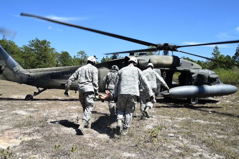 Airmen from Joint Task Force-Bravo 612th Air Base Squadron Fire Department practice loading a simulated crash victim onto a U.S. Army UH-60 Black Hawk helicopter during a personnel recovery exercise, March 10, 2016, near Soto Cano Air Base, Honduras. This was the first participation of firefighters during JTF-Bravo's quarterly personnel rescue practices, testing their abilities to respond to this type of mission. (U.S. Army photo by Martin Chahin/Released)