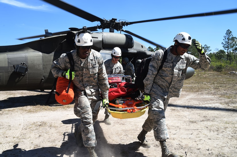 Airmen with Joint Task Force-Bravo 612th Air Base Squadron Fire Department, practice unloading rescue equipment from a U.S Army UH-60 Black Hawk helicopter during a simulated personnel recovery exercise, March 10, 2016 near Soto Cano Air Base, Honduras. The Fire Department supported the exercise with their extrication capabilities and equipment, testing their ability to respond to a personnel recovery mission. (U.S. Army photo by Martin Chahin/Released)