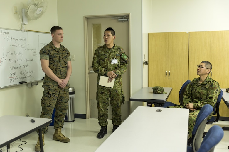 Japan Ground Self-Defense Force Sgt. Aranami, interpreter trainee, translates for Lance Cpl. Healy, left, an ordnanceman with Marine Aerial Refueler Transport Squadron 152, as he gives Marine Corps Air Station Iwakuni, Japan's, command brief during the Public Affairs Office's annual English seminar on Marine Corps Air Station Iwakuni, Japan, March 16, 2016. The seminar is held annually by the station Public Affairs Office to help improve upon the JGSDF's understanding and use of the English language prior to their deployment in support of exercises in both the United States and Japan.  (U.S. Marine Corps photo by Sgt. Antonio J. Rubio/Released)