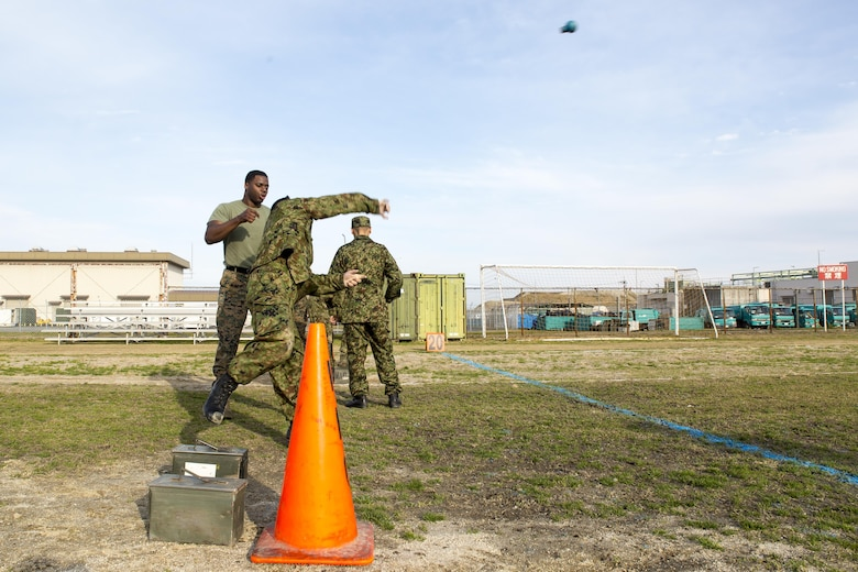 Japan Ground Self-Defense Force Sgt. 1st Class Iwamoto, Japanese interpreter instructor, throws a rubber grenade while conducting a combat fitness test during the Public Affairs Office's annual English seminar on Marine Corps Air Station Iwakuni, Japan, March 16, 2016. The seminar is held annually by the station Public Affairs Office to help improve upon the JGSDF's understanding and use of the English language prior to their deployment in support of exercises in both the United States and Japan.  (U.S. Marine Corps photo by Sgt. Antonio J. Rubio/Released)