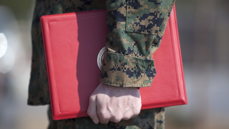 Cpl. Joseph Currey grips his award during an award ceremony at Marine Corps Air Station Cherry Point, North Carolina, March 1, 2016. Currey was awarded the Navy and Marine Corps Commendation Medal for his actions after witnessing an ambulance wreck. Currey demonstrated his devotion to serving others as he placed the well-being of the injured personnel above his own by running towards the scene of an accident and rendering aide to those need. Currey is an air support operations operator with Marine Aviation Support Squadron 1.