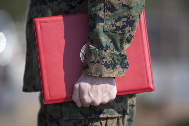 Cpl. Joseph Currey grips his award during an award ceremony at Marine Corps Air Station Cherry Point, N.C., March 1, 2016. Currey was awarded the Navy and Marine Corps Commendation Medal for his actions after witnessing an ambulance wreck. Currey demonstrated his devotion to serving others as he placed the well-being of the injured personnel above his own by running towards the scene of an accident and rendering aide to those need. Currey is an air support operations operator with Marine Aviation Support Squadron 1. (U.S. Marine Corps photo by Cpl. Austin A. Lewis, U.S. Marine Corps caption by Cpl. N.W. Huertas/Released)