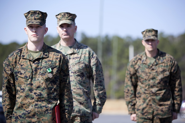 Cpl. Joseph Currey, left, stands in front of Lt. Col. Jeremy Winters , center, and Sgt. Maj. Jeffrey Durham after receiving an award at Marine Corps Air Station Cherry Point, N.C., March 1, 2016. Currey was awarded the Navy and Marine Corps Commendation Medal for his actions after witnessing an ambulance wreck. Currey demonstrated his devotion to serving others as he placed the well-being of the injured personnel above his own by running towards the scene of an accident and rendering aide to those need. Currey is an air support operations operator with Marine Aviation Support Squadron 1. Winters is the commanding officer of the squadron and Dunham is the squadron sergeant major. (U.S. Marine Corps photo by Cpl. Austin A. Lewis, U.S. Marine Corps caption by Cpl. N.W. Huertas/Released)