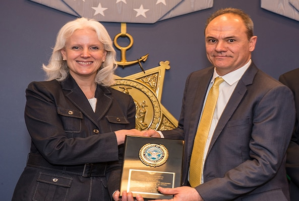 Ms. Kristen Baldwin, acting deputy assistant secretary of defense, systems engineering (left) presents an award for achievement in defense standardization to John Bonitatibus, electronics engineer at Defense Logistics Agency Land and Maritime inside the Hall of Heroes at the Pentagon, March 16, 2016.