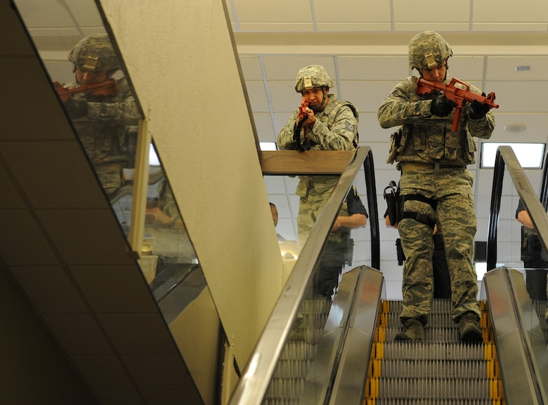 Tech. Sgt. James Herrera, 81st Security Forces Squadron operations NCO in charge, and Staff Sgt. Cody Berry, 81st SFS ?, survey the area for gunmen during Keesler's active shooter exercise at the Keesler Medical Center Mar. 17, 2016, Keesler Air Force Base, Miss.  An active duty Air Force member simulated opening fire at the hospital to test the base's ability to respond to and recover from a mass casualty event. (U.S. Air Force photo by Kemberly Groue)