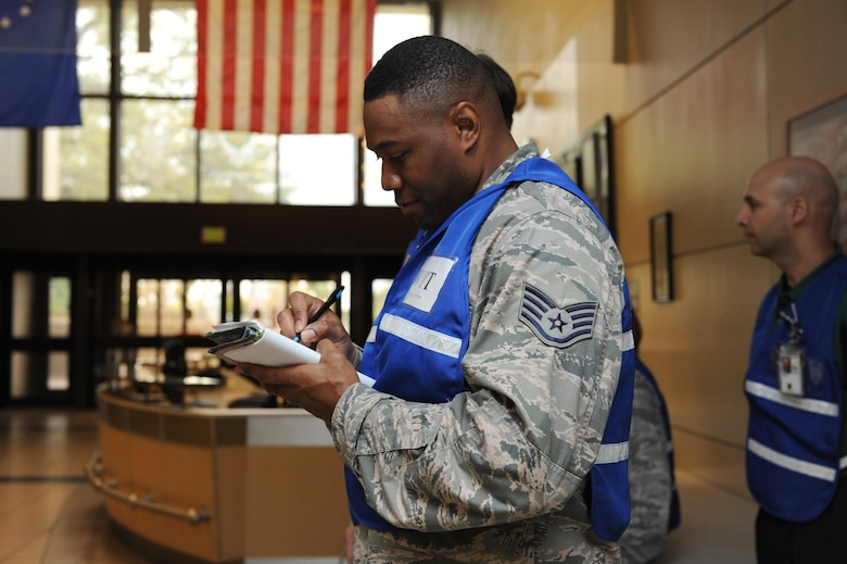 Staff Sgt. Detrick Jack, 81st Security Forces Squadron standardization evaluations NCO in charge and Wing Inspection Team member, takes notes during Keesler's active shooter exercise at the Keesler Medical Center Mar. 17, 2016, Keesler Air Force Base, Miss.  An active duty Air Force member simulated opening fire at the hospital to test the base's ability to respond to and recover from a mass casualty event. (U.S. Air Force photo by Kemberly Groue)