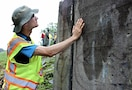 Alex Baldowski, Baltimore District civil engineer, checks for cracking in a floodwall in Johnson City, New York, July 8, 2015. The condition of floodwalls is an important part of the levee inspection checklist to determine how the levee may perform during the next flood. The levee was built by the Corps, and New York State Department of Environmental Conservation operates and maintains the levee.
