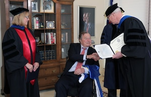 National Intelligence University President Dr. David Ellison presents an honorary degree to the Honorable George H.W. Bush in Houston, Texas on March 8, 2016.