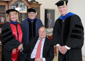 The Honorable George H.W. Bush shakes hands with NIU Provost Dr. Susan Studds (left) and is joined by Dr. Don Hanle, Dean of the College of Strategic Intelligence (center), and NIU President Dr. David Ellison (right).
