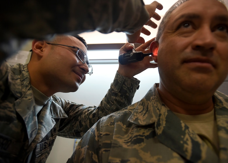 Senior Airman Jherico Guerrero, 559th Medical Group Public Health Technician, checks a patient's ear prior to administering a hearing test at the Deployment Related Health Clinic, part of the 59th Medical Wing Base Operational Medicine Clinic at the Wilford Hall Ambulatory Surgical Center, Joint Base San Antonio-Lackland, Texas, Feb 24. The DRHC will see approximately 250 members a month for deployment health assessments. (U.S. Air Force photo/Staff Sgt. Kevin Iinuma)