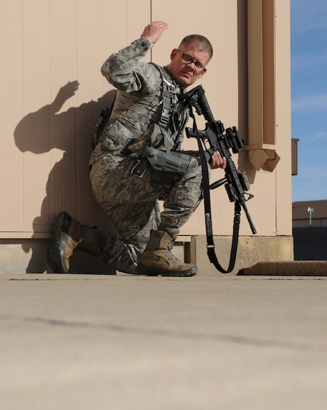 Tech. Sgt. Steven Groff, 28th Security Forces Squadron flight chief, signals for his partner to advance during a training exercise at Ellsworth Air Force Base, S.D., Feb. 10, 2016. Training exercises ensure defenders are ready to perform their duty at any time, whether at home or deployed. (U.S. Air Force photo by Airman 1st Class Denise M. Nevins/Released)