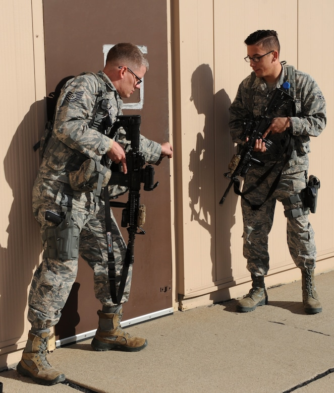 Tech. Sgt. Steven Groff, 28th Security Forces Squadron flight chief, and Airman 1st Class Christopher Dominguez, 28th SFS response force member, prepare to search a building on the flightline during a training exercise at Ellsworth Air Force Base, S.D., Feb. 10, 2016. Defenders must be ready at a moment's notice for any situation that may occur, whether it be a drunken driver or an active shooter. (U.S. Air Force photo by Airman 1st Class Denise M. Nevins/Released)