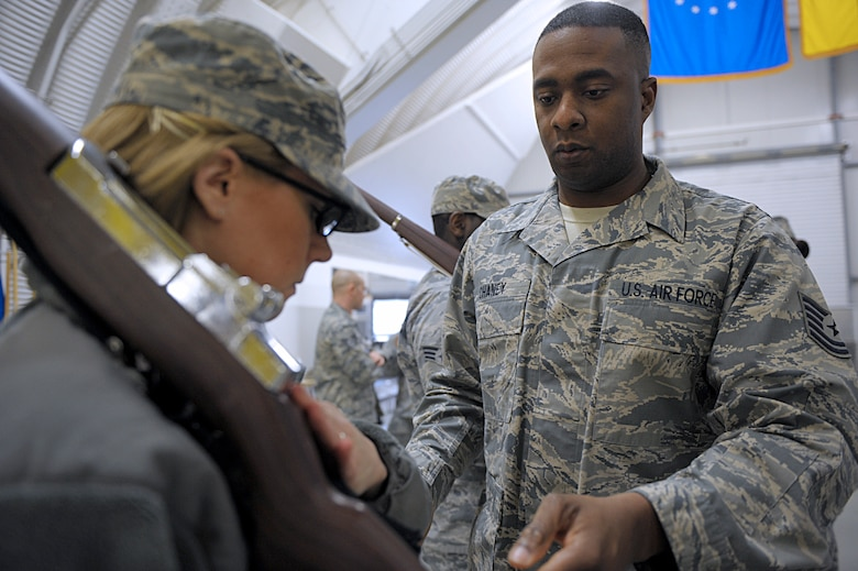 Tech. Sgt. Maurice Chaney, U.S. Air Force Honor Guard Drill Team NCO in charge, corrects the rifle and hand placements of Airman 1st Class Kara Woods, 86th Communications Squadron administrator, March 15, 2016, at Ramstein Air Base, Germany. Members from the U.S. Air Force Honor Guard traveled to Ramstein to teach base honor guardsmen techniques to better hone their performances. (U.S. Air Force photo/Staff Sgt. Timothy Moore)