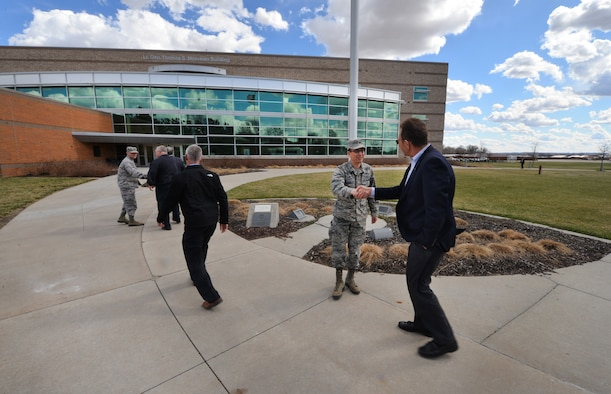 U.S. Air Force Col. William Carle, 557th Weather Wing commander, greets John Hansen, Offutt Advisory Council president and 55th Wing's honorary commander, and other OAC members as they arrive at the 557th WW headquarters facility March 16. The OAC toured the facility and learned more about the wing's mission during the special event. (Photo by Josh Plueger)