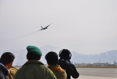"An Afghan Air Force C-130 Hercules flies over the crowd at the ""Re-birth of the Afghan Air Force"" event at Hamid Karzai International Airport, Kabul, Afghanistan, Feb. 11, 2016.  Afghan President Ashraf Ghani addressed the Afghan National Army, AAF and coalition partners, and spoke of the capabilities of the A-29, MD-530F, C-130, Mi-17, PC-12 and C-208 aircraft. He also praised the young air force for their efforts in the 2015 Fighting Season and Winter Campaign. The flying service was re-established in 2008 after it had ceased to exist following the collapse of the Soviet-backed Afghan regime in 1992. (U.S. Air Force photo by Capt. Eydie Sakura/released)"