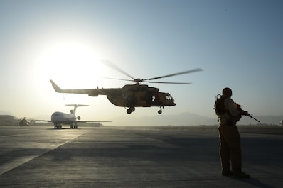 A Train, Advise, Assist Command-Air (TAAC-Air) security forces members stands guard as an Afghan Air Force Mi17 helicopter takes off at Hamid Karzai International Airport, Kabul, Afghanistan, Sept. 27, 2015. (U.S. Air Force photo by Staff Sgt. Sandra Welch/released)