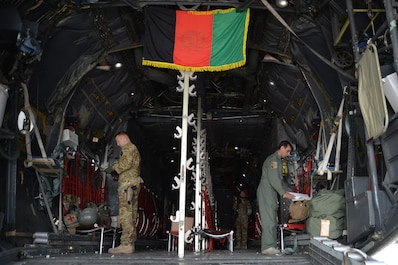 A Train, Advise, Assist Command-Air (TAAC-Air) advisor (left) and his Afghan Air Force counterpart (right) prepare the back of a C-130 for a mission at Hamid Karzai International Airport, Kabul, Afghanistan, Sept. 22, 2015. (U.S. Air Force photo by Staff Sgt. Sandra Welch/released)