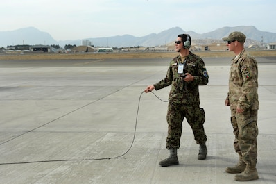 An Afghan Air Force crew chief and Train, Advise, Assist Command-Air (TAAC-Air) advisor, prepare an aircraft for flight at Hamid Karzai International Airport, Kabul, Afghanistan, Sept. 22, 2015. (U.S. Air Force photo by Staff Sgt. Sandra Welch/released)