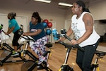 Ahawana Williams, Anita Elum-Mason and Ieshia Clark, all from DLA Installation Support, participate in a cycling class at the HQC Fitness Center. They are among more than 200 employees taking part in the 12-week Winter Warrior Challenge.