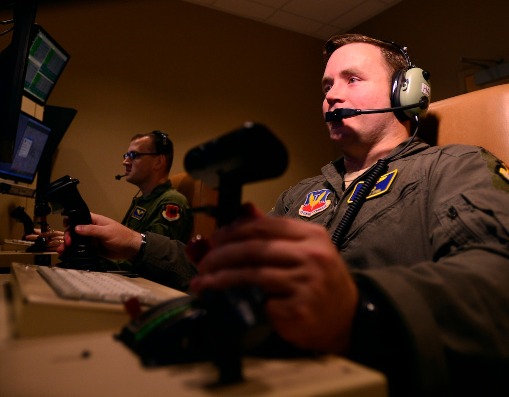 Capt. Jonathan, 432nd Wing pilot, left, and Staff Sgt. Matthew, 432nd WG sensor operator, right, fly a training mission Oct. 13, 2015, at Creech Air Force Base, Nevada. The 432nd Wing conducted 189 weapon strikes in July of 2015 and 249 in August, setting a record for the number of strikes in a month in support of Operation Inherent Resolve. (U.S. Air Force photo by Airman 1st Class Christian Clausen/released)