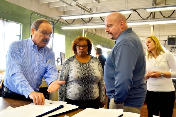 Alessandro Marcozzi, a manager at DeRossi & Son in Vineland, New Jersey, explains the clothing manufacturing process to Defense Logistics Agency Troop Support employees Robin-Kirkland Gonzalez, customer account specialist, Ken Drexinger, demand planner, and Jessica De La Hoz, contracting officer, all with the Clothing and Textiles supply chain during a visit to plant March 2.