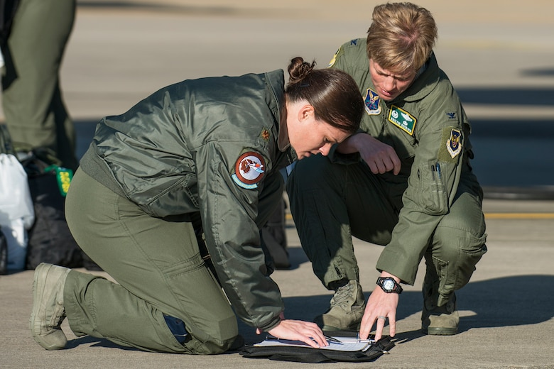U.S. Air Force Maj. Heather Decker, of the 93rd Bomb Squadron, and Col. Kristin Goodwin, commander of the 2nd Bomb Wing, look over aircraft forms prior to a mission on Mar. 22, 2013, Barksdale Air Force Base, La. In recognition of Women's History Month, the mission consisted of two B-52H Stratofortress bombers flown by two all-female aircrews made up from members of the Air Force Reserve Command's 93rd and 343rd Bomb Squadrons and the 2nd Bomb Wing's 11th, 20th and 96th Bomb Squadrons. (U.S. Air Force photo by Master Sgt. Greg Steele/Released)