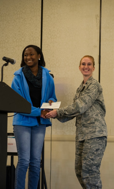 Lt. Col. Mary Jeffrey, 315th Operations Group executive officer, congratulates Shanyla Moultrie, of Cane Bay High School, for placing third place in the Women in Aviation Career Day essay contest. Over 130 middle and high school girls from 12 Lowcountry schools visited Joint Base Charleston March 22 to learn about jobs in aviation as part of the 315th Airlift Wing's 9th annual Women in Aviation Career Day.	(U.S. Air Force photo by Senior Airman Jonathan Lane)