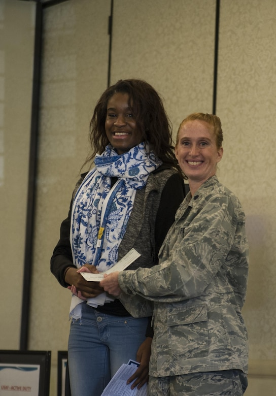 Lt. Col. Mary Jeffrey, 315th Operations Group executive officer, congratulates Ogugua Nwaezeigwe, Cane Bay High School,  for winning first place in the Women in Aviation Career Day essay contest.Over 130 middle and high school girls from 12 Lowcountry schools visited Joint Base Charleston March 22 to learn about jobs in aviation as part of the 315th Airlift Wing's 9th annual Women in Aviation Career Day. (U.S. Air Force photo by Senior Airman Jonathan Lane)