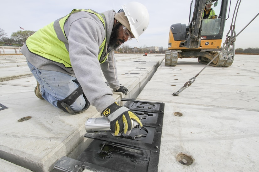 ARLINGTON, Va. – Darian Moon, a contractor working on the Arlington National Cemetery's Millennium Project paints identification numbers on the top off a pre-cast, pre-placed double-depth-concrete liner, March 22, 2016. The liners are a first for the cemetery and will maximize burial opportunities within the 27 acre expansion project. (U.S. Army photo/Patrick Bloodgood)