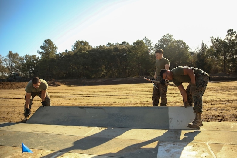 U.S. Marines with Marine Wing Support Squadron 272 construct a vertical take-off and landing pad during a Marine Corps Combat Readiness Evaluation at Marine Corps Auxiliary Landing Field Bogue, N.C., March 17, 2016. The MCCRE, which went from March 14-18, tested MWSS-272's ability to build an AM-2 aluminum matting V/TOL pad ready to accept incoming aircraft. MWSS-272 is part of Marine Aircraft Group 26, 2nd Marine Aircraft Wing.(U.S. Marine Corps photo by Cpl. Kaitlyn V. Klein/Released)