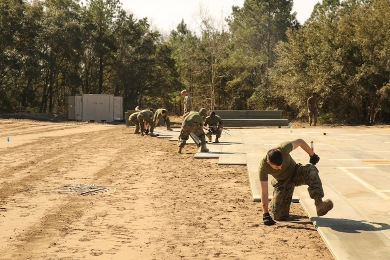 U.S. Marines with Marine Wing Support Squadron 272 construct a vertical take-off and landing pad during a Marine Corps Combat Readiness Evaluation at Marine Corps Auxiliary Landing Field Bogue, N.C., March 17, 2016. The MCCRE, which went from March 14-18, tested MWSS-272's ability to build an AM-2 aluminum matting V/TOL pad ready to accept incoming aircraft. MWSS-272 is part of Marine Aircraft Group 26, 2nd Marine Aircraft Wing. (U.S. Marine Corps photo by Cpl. Kaitlyn V. Klein/Released)