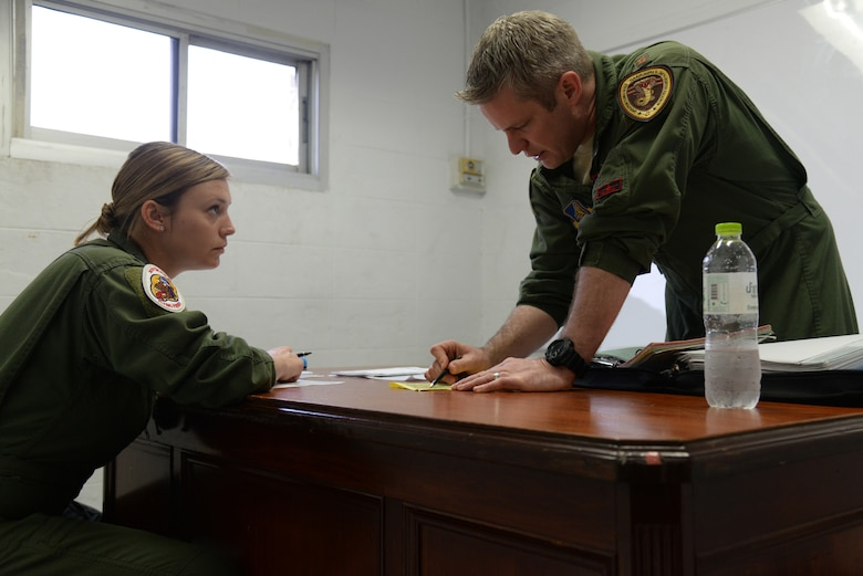 U.S. Air Force 1st Lt. Brittany Trimble, 36th Fighter Squadron pilot, receives a mission briefing from her flight lead Maj. Shawn Walsh, 36th FS director of staff, Feb. 15, 2016, at Korat Royal Thai Air Force Base, Thailand. Coming straight from B Course, Trimble has only been flying actively with the 36th FS since October 2015 and is one of the newest wingmen in the squadron. (U.S. Air Force photo by Staff Sgt. Amber E. Jacobs)