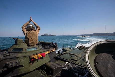 U.S. Marine Cpl. Christopher Lee, with Alpha Company, Battalion Landing Team 1st Battalion, 5th Marines, 31st Marine Expeditionary Unit, uses hand signals to communicate with other AAV-P7/A1 Amphibious Assault Vehicles while conducting a combined amphibious assault on Dogu Beach, South Korea, as part of Ssang Yong 16, March 12, 2016. Ssang Yong is a biennial combined amphibious exercise conducted by U.S. forces with the Republic of Korea Navy and Marine Corps, Australian Army and Royal New Zealand Army forces in order to strengthen interoperability and working relationships across a wide range of military operations. The Marines and sailors of the 31st MEU are in Korea as part of their spring deployment to the Asia-Pacific region. Lee, a native of Haslet, Texas, is a crew chief with Alpha Co., BLT 1/5,31st MEU. (U.S. Marine Corps photo by Lance Cpl. Carl King Jr./Released)
