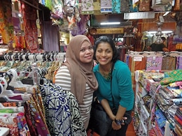 160314-N-IE405-100 KUALA LUMPUR, Malaysia (Mar. 14, 2016) - Mass Communication Specialist 2nd Class Indra Bosko, assigned to U.S. 7th Fleet, poses with a Malay salesperson at a batik shop in Central Market. U.S. 7th Fleet is on patrol in the 7th Fleet area of operations in support of security and stability in the Indo-Asia-Pacific. (Photo by Viji Vengadasalam/Released)