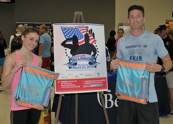 Erin Hunt with Defense Logistics Agency Strategic Materials and Air Force Capt. Brandon Bryan from the Air Force Petroleum Agency show off prizes they won as the first place female and male runners in the Spring Fling 5K at Fort Belvoir, Virginia, March 20.