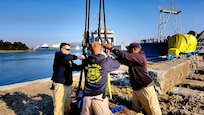 Soldiers from the 511th Engineer Dive Detachment prepare to remove slings from a concrete pier being removed from the water. The active duty unit removed a dozen 10,000 pound pilings at the reserve center as part of a Troop Construction project, saving the Army money while performing real world training.