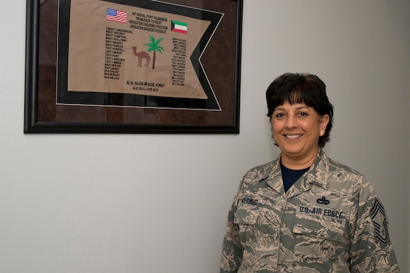 U.S. Air Force Reserve Chief Master Sgt. Cynthia Underwood, the air transportation superintendent for the 96th Aerial Port Squadron, poses for a photo at Little Rock Air Force Base, Ark., Mar. 4, 2016. The memento flag details the date, time and place of her deployment, which she described as one of the highlights of her Air Force career. (U.S. Air Force photo by Master Sgt. Jeff Walston/Released)