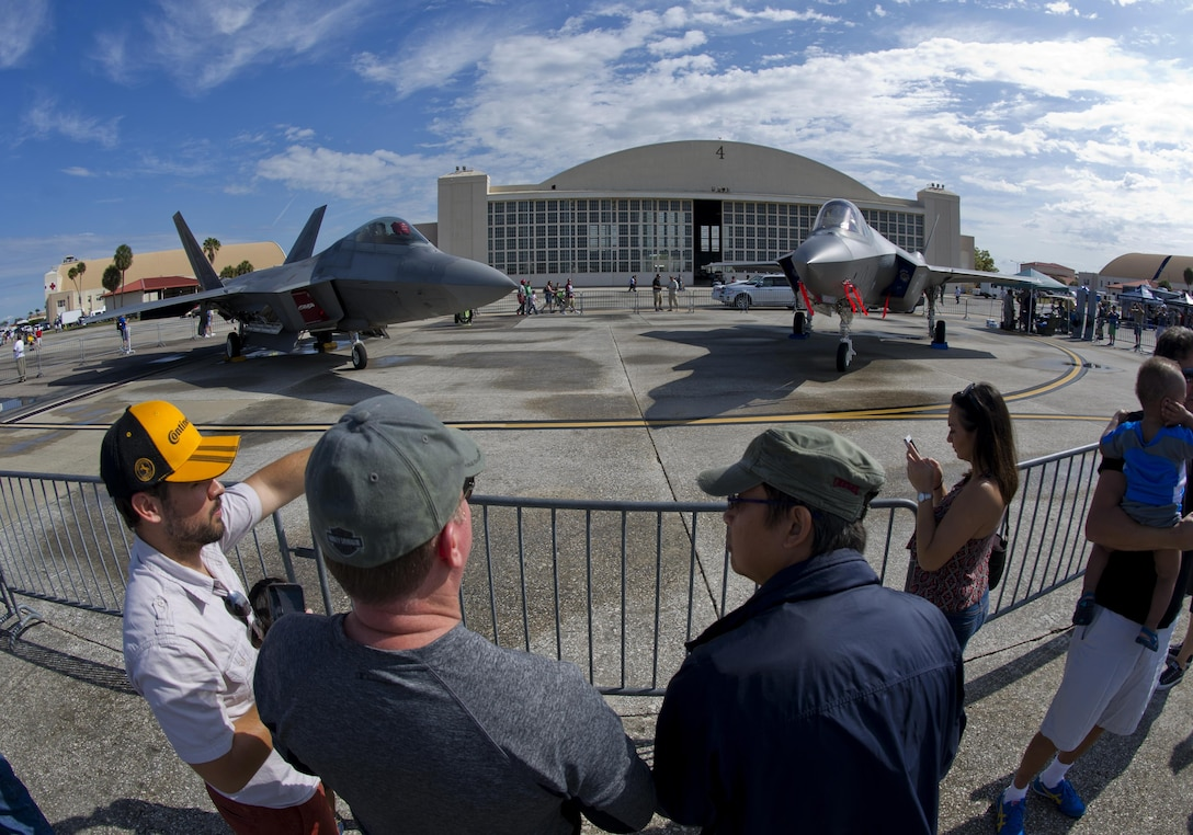 Attendees of the Tampa Bay AirFest 2016 talk about the F-22 Raptor and F-35 Lightning II at MacDill Air Force Base, Fla., March 20, 2016.  MacDill was host to spectacular aerial demonstrations, static displays and featured the U.S. Air Force Air Demonstration Squadron Thunderbirds, giving the Tampa Bay community the opportunity to witness firsthand the capabilities of the armed forces. (U.S. Air Force photo by Senior Airman Alex Fox Echols III/Released)