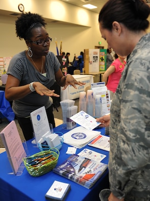 Nakisha Hall, 81st Force Support Squadron community readiness specialist, explains what the Airman and Family Readiness Center has to offer to Lt. Col. Elizabeth Aptekar, 335th Training Squadron commander, during the National Women's History Fair at the Roberts Consolidated Maintenance Facility Mar. 24, 2016, Keesler Air Force Base, Miss. The event was held in honor of National Women's History Month.  Also included, were health and informational booths, a guest panel of accomplished women and a presentation honoring Keesler women of distinction.  (U.S. Air Force photo by Kemberly Groue)