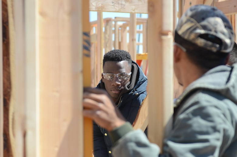 A cadet from the U.S. Air Force Academy stands inside the frame of a home he and other cadets and Habitat for Humanity volunteers are building for a lower-income family in Oklahoma City, Oklahoma, March 22, 2016. (U.S. Air Force photo/Harry Lundy)