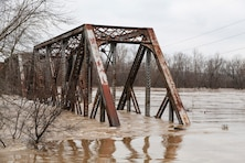 A railway bridge gets swallowed by the Meramec River.  (Photo by USACE, St. Louis District)