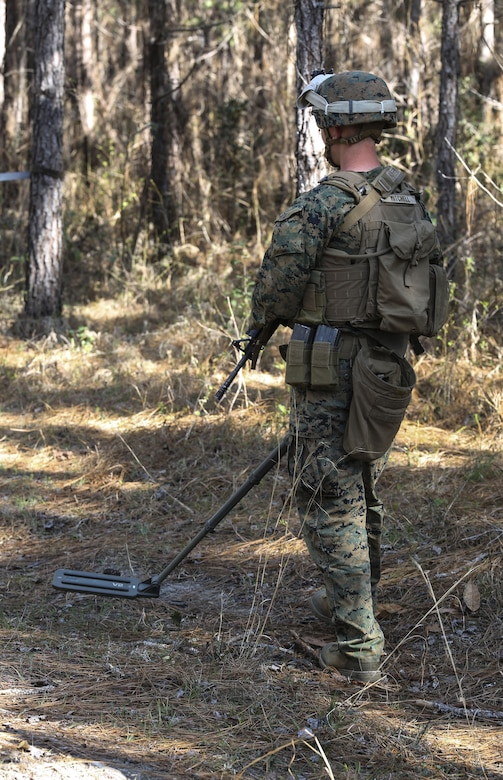 Lance Cpl. Luke T. Mitchell, a combat engineer with 2nd Combat Engineer Battalion, searches for improvised explosive devices using a compact metal detector during the counter-IED portion of the battalion's sapper squad competition at Camp Lejeune, N.C., March 22, 2016. The counter-IED portion of the competition put squads' observation skills to the test as they swept a lane of simulated IEDs. (U.S. Marine Corps photo by Cpl. Paul S. Martinez/Released)