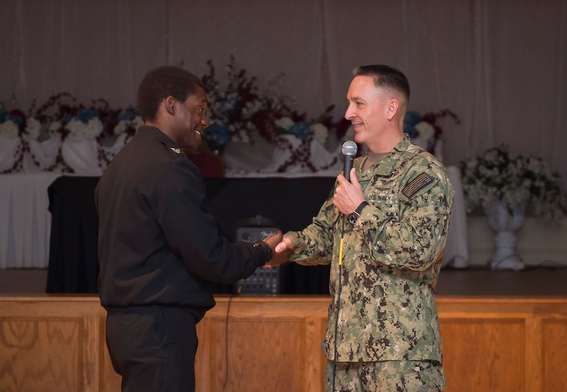 Petty Officer 3nd Class Labaron Johnson is coined by the Master Chief Petty Officer of the Navy, Mike Stevens, during an all hands event at the Joint Base Charleston – Weapons Station, S.C., March 24, 2016. Stevens was visiting the base as part of a two-week tour of East Coast military bases, from Norfolk, Virginia to Key West Fla.  Stevens wanted to communicate face-to-face with Sailors. (U.S. Air Force photo/Staff Sgt. Jared Trimarchi)