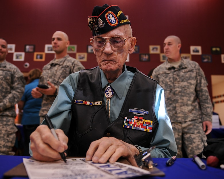 Retired U.S. Air Force Master Sgt. William Lyle Eldridge, Bataan Death March survivor, signs a runner's certificate prior to the start of the 2016 Bataan Memorial Death March at White Sands Missile Range, N.M., March 18, 2016. The 26.2-mile march is designed to show participants what the prisoners of war at Bataan endured. In reality, however, the POWs marched more than 60 miles without food or water, while many were beaten and some never made it to the end. (U.S. Air Force photo by Senior Airman Harry Brexel)