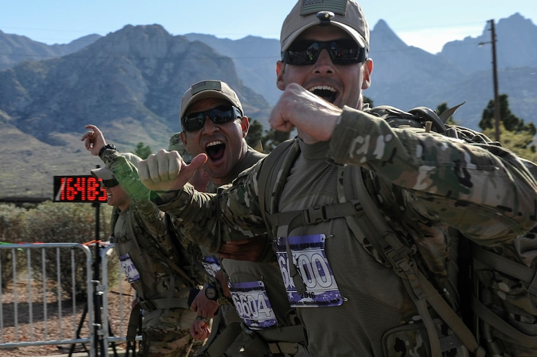Peruvian Air Force exchange Officer Maj. Javier Camacho, center, and U.S. Air Force 1st Lt. Corbin Aldridge, 19th Logistics Readiness Squadron aerial port flight commander, cross the finish line of the 27th annual Bataan Memorial Death March, at White Sands Missile Range, N.M., March 20, 2016. The 19th LRS team completed the World War II memorial ruck march in less than nine hours. (U.S. Air Force photo by Senior Airman Harry Brexel)